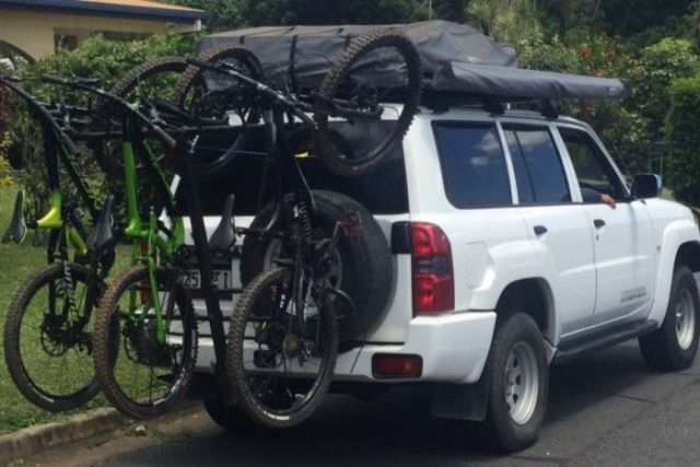 a car with five bikes on the back covering the rego