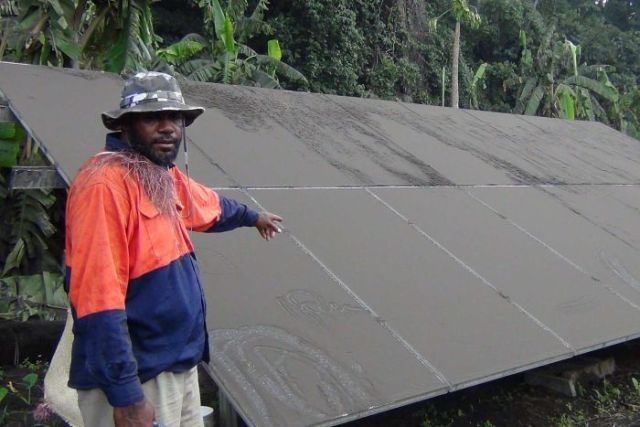 A man stands beside what appears to be a solar panel covered in ash.