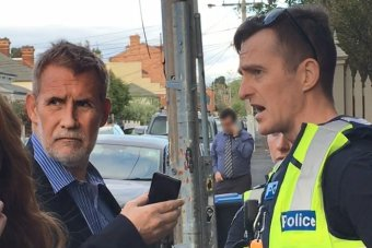 Phillip Whiteman on a suburban street holding a phone, standing opposite a police officer.