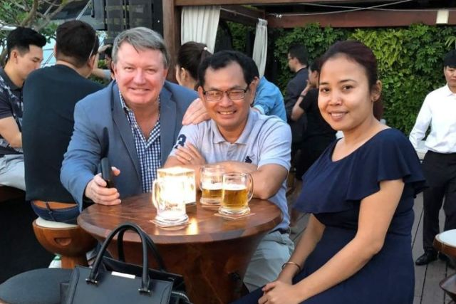 Bill Clough, Kay Kimsong and Heang Tangmeng at a table, having a drink.