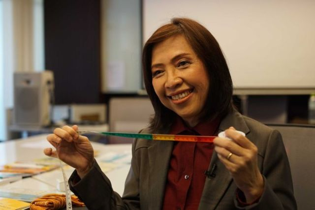 A woman wearing a smart jacket smiles as she holds up a tape measure.