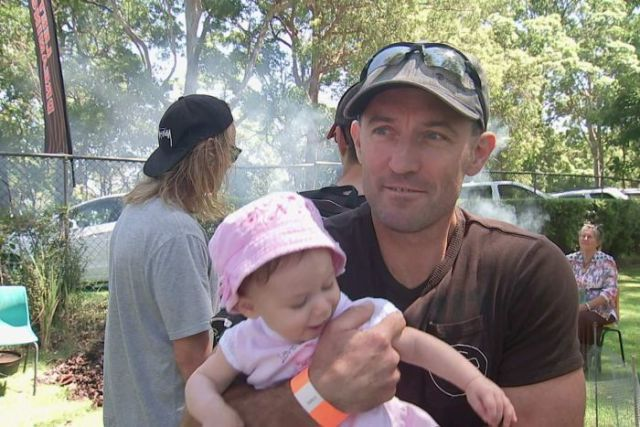Man holding a baby at a local show at Mount Tamborine.