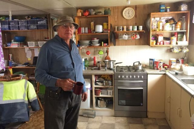 Rodney West holding a mug while standing in the kitchen of his houseboat, which is crammed with household belongings.
