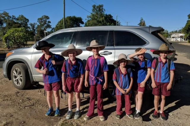 Six kids stand in front of silver SUV car wearing school uniforms, backpacks and broad brimmed hats