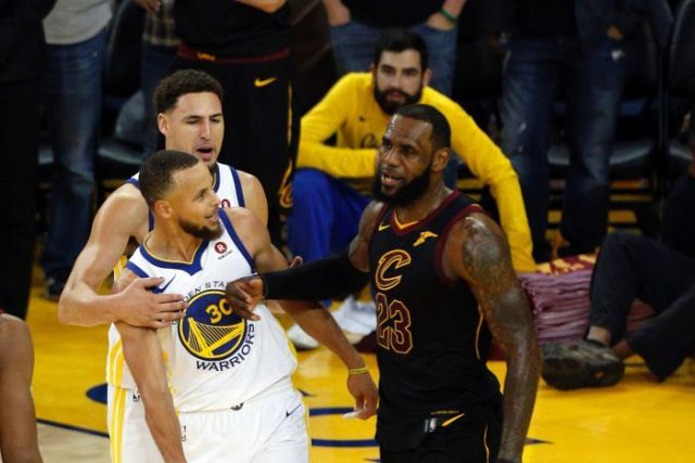 LeBron James pushes Steph Curry with his forearm as Kaly Thompson pulls Curry away.