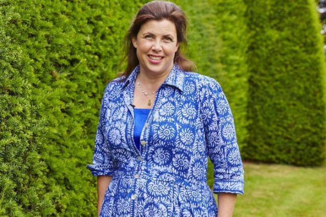 UK TV presenter Kirstie Allsopp, who has brown hair and wearing a blue dress, stands next to a row of hedges.