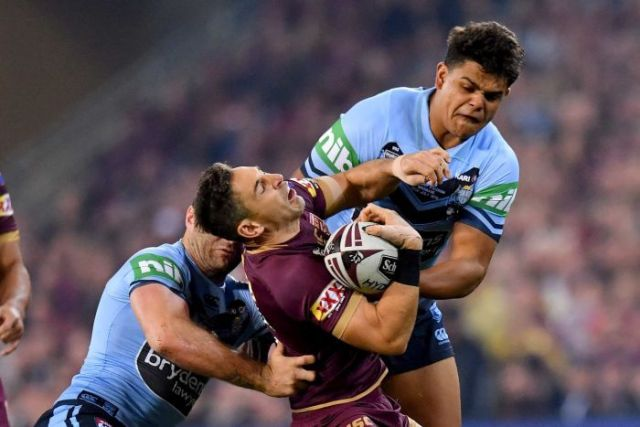 Billy Slater (C) of the Maroons is tackled by the Blues in State of Origin III in Brisbane on July 11, 2018.