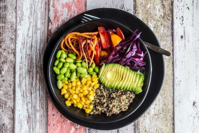 A black bowl full of quinoa, avocado, edamame, tomatoes, corn, red cabbage and carrots sits on a wooden table.