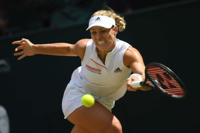 Angelique Kerber stretches for a shot with a grimaced expression on her face.