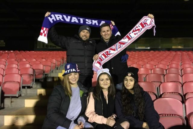 Croatian-Australian football fans in the stands at a Melbourne stadium hold scarfs.
