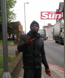 THE SUN LOGO MANDATORY: THIS IMAGE IS MADE AVAILABLE UNDER THE CONDITION THAT THE SUN LOGO REMAIN IN THE FRAME - This image taken from video made available by The Sun newspaper shows what appears to be one of the attackers speaking to the camera, holding a knife and a cleaver in his bloodied hands, after a brutal attack in broad daylight Wednesday, May 22, 2013 near a military barracks in London. The attack just a few blocks from the Royal Artillery Barracks in the Woolrich neighborhood of London left one man dead and two suspects hospitalized after a shootout with police. British Prime Minister David Cameron said the attack appeared to be terror related. There was no immediate way for The Associated Press to verify who the cameraperson was. (AP Photo/The Sun) UNITED KINGDOM OUT INTERNET OUT ONLINE OUT   NO ARCHIVE NO SALES  NO USE AFTER  19:30 GMT THURSDAY MAY 23
