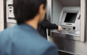 Man withdrawing cash at an ATM with a thief following him