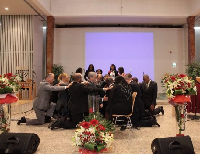 De predikanten knielen om ds. Elizabeth