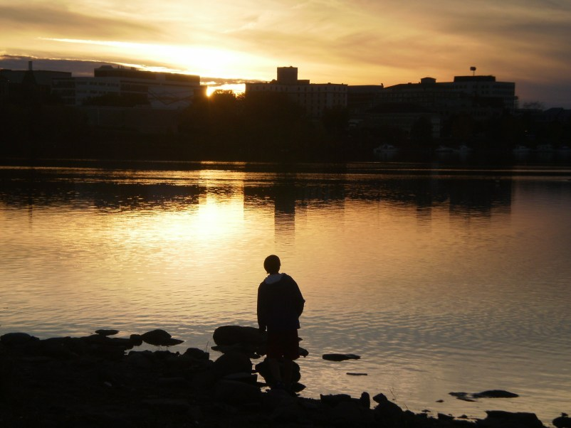 silhouette of a boy at river's edge at sunset