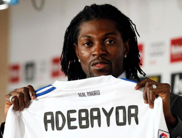 Former Manchester City player Emmanuel Adebayor holds up his new Real Madrid jersey during his presentation at the Santiago Bernabeu stadium in Madrid, January 27, 2011. Adebayor was signed on loan until the end of the season. REUTERS/Sergio Perez (SPAIN - Tags: SPORT SOCCER)