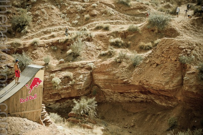 A wooden jump leads up to a massive canyon gap at the Red Bull Rampage downhill mountain biking event in Utah.