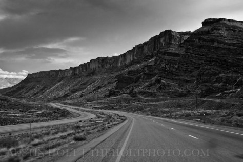 Tall, rocky mesas overlook the highway that stretches into the town of Moab, Utah.