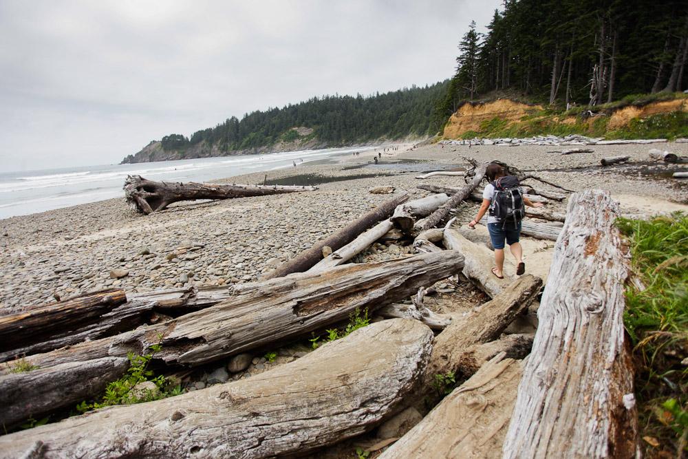 Re Wikstrom walking on logs on the beach in Oregon