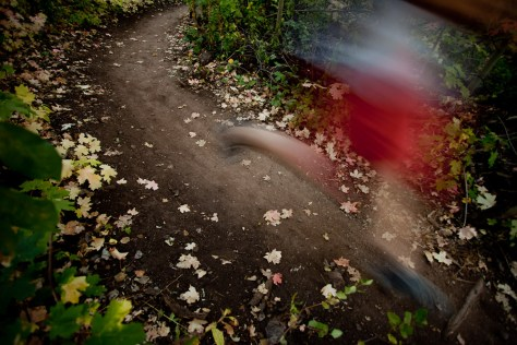 A trail runner blurs down the trail and over fallen leaves in Park City, Utah