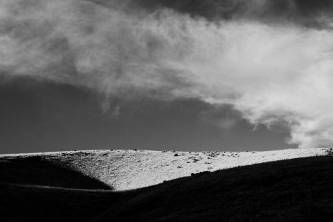 A cloud hovers over a low, rolling hill in Utah.