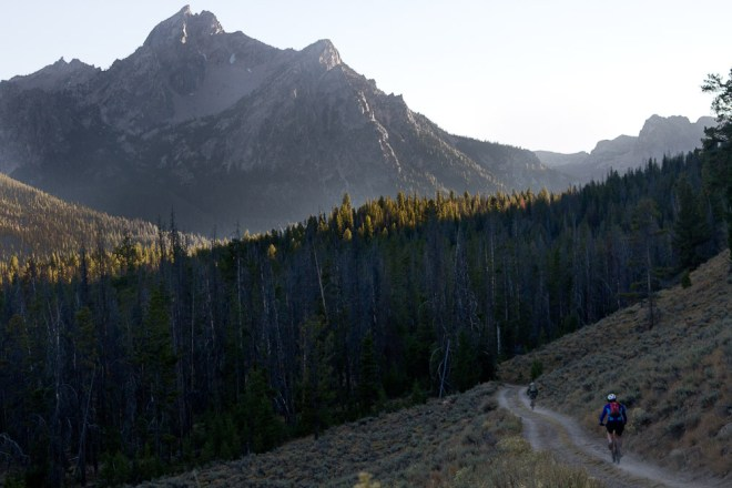 Two mountain bikers ride a dirt road toward a mountain in the Sawtooths in Idaho.