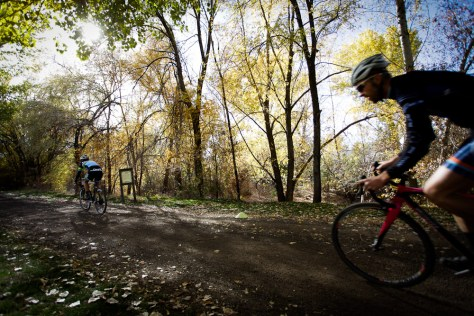 A bike racer chases down another rider on a dirt trail at the UTCX cyclocross bike race.