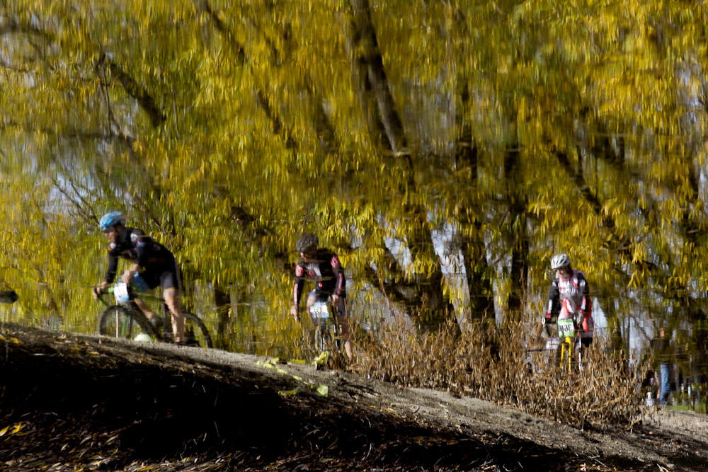 A reflection of a group of bike racers riding past a river at the UTCX cyclocross race.