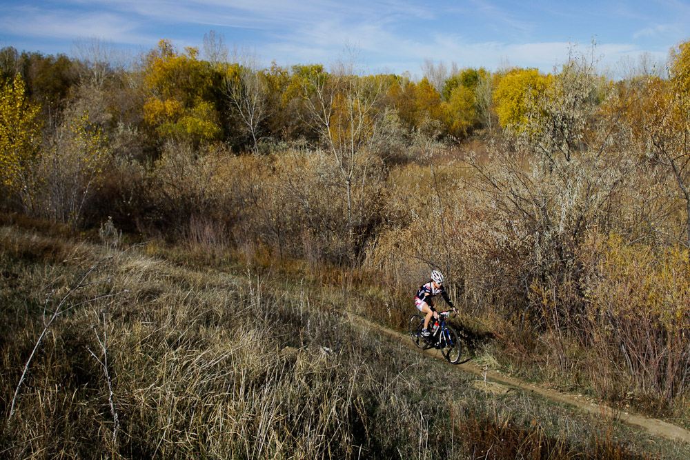 A lone bike racer rides along a strip of dirt trail at the UTCX cyclocross race at Soldier Hollow park in Salt Lake City, Utah.