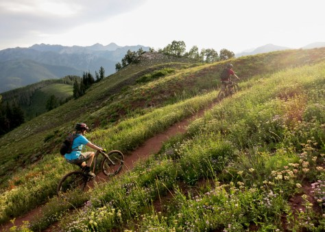 Jen and Adam pedal into a gorgeous sunset along the Crest and the trail is flanked by wildflowers and an epic view of the surrounding mountains.