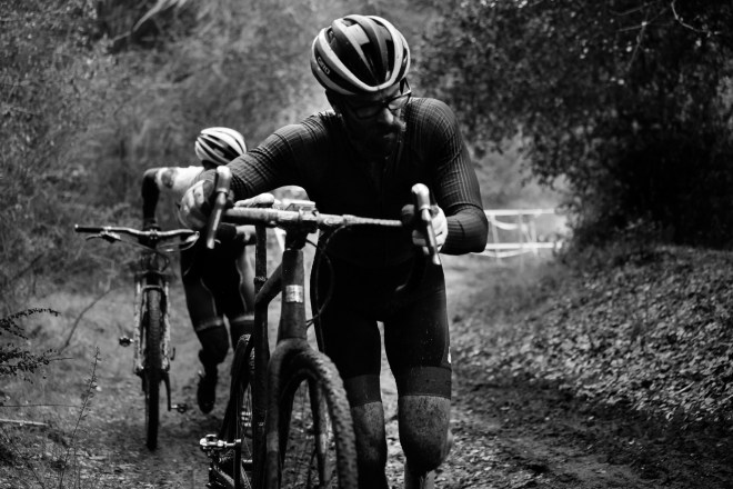 Santa Cruz rider Justin Chapin running up a steep muddy hill at a cyclocross race.