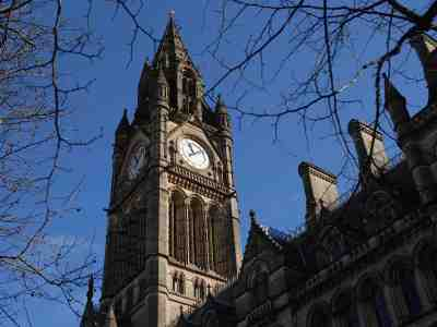 Looking up at Manchester Town Hall clock tower against a blue sky