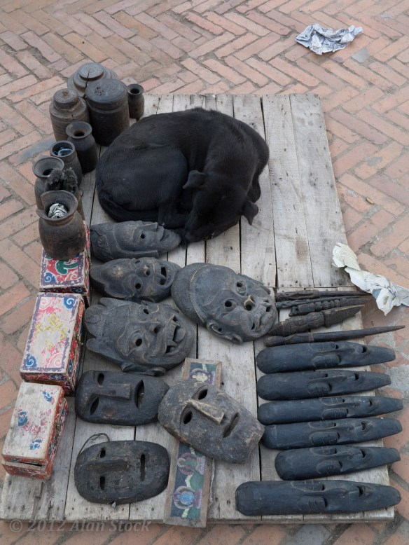 A dog sleeps next to souvenir masks at the Durbar Square