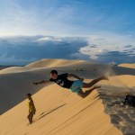 Travelmate Backpacker jumping Superman midair sand dunes Moi Ne Vietnam