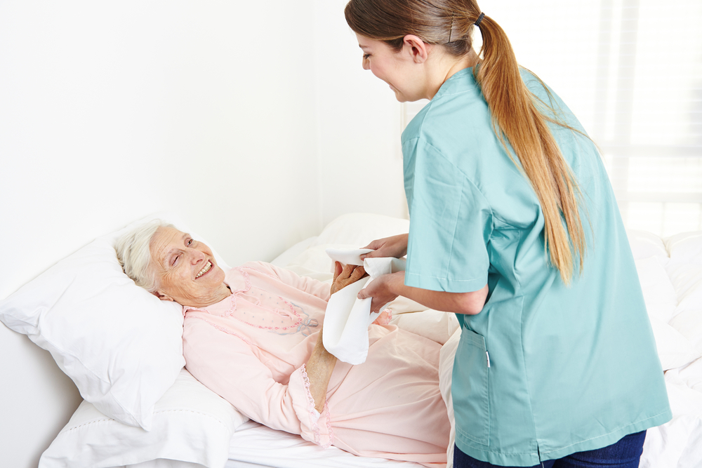Geriatric nurse washing bedridden senior woman and drying her hands