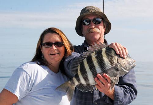 Capt. Deidra Helmey Jeffcoat and husband Danny holding up a nice ocean sheepshead.