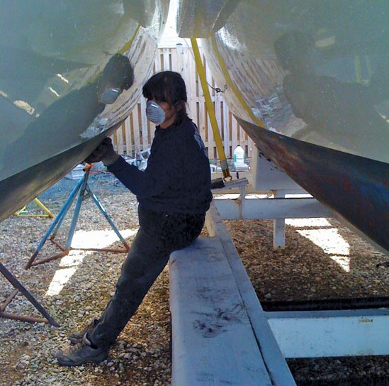 """Terry Boram sanding one of the amas of her trimaran, """"Tri Dreaming."""""""