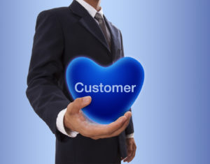 Businessman hand holding blue heart bubble with customer word