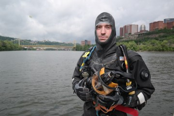 Greg Tersine, a diver for the Pittsburgh Police Department's River Rescue Unit, shows off his vulcanized rubber diving suit. Photo: Lou Blouin