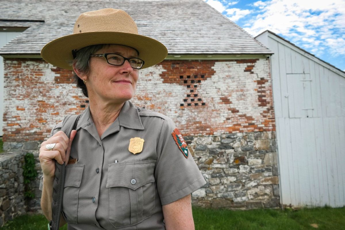 Park ranger Katie Lawhon stands near the Trostle Farm, Gettysburg National Military Park, June 17, 2015. The barn dates back to the time of the battle and is a favorite with tourists because of the cannonball hole left in the brick wall during the second day of the battle. Photo: Lou Blouin