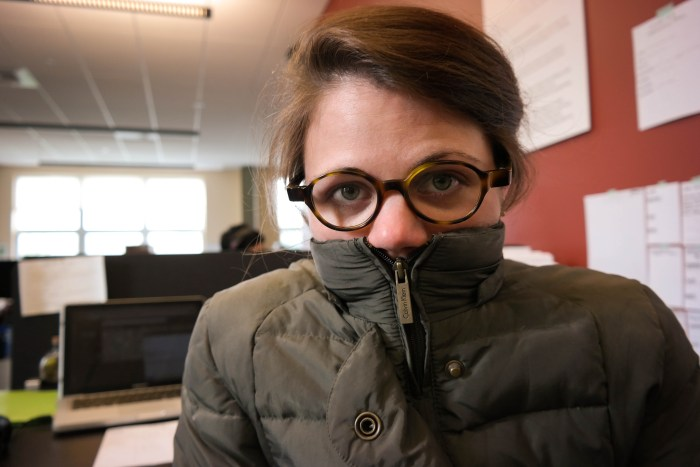 It's a hot summer. But overly cool office temperatures mean that WESA reporter Margaret Krauss still has to bundle up to be comfortable at Pittsburgh's Community Broadcast Center. Photo: Lou Blouin