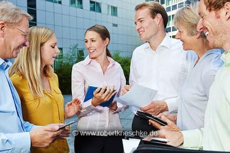 Diskussion in einem dynamischen Business Team mit Tablet Computer im Freien