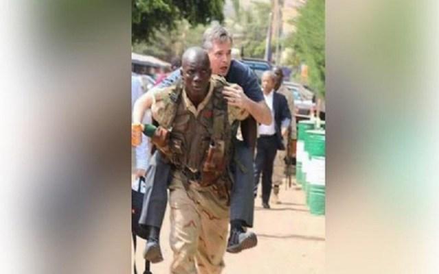 جندي مالي يحمل سائحا على ظهره