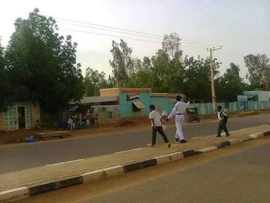 شرطي بالمرور السوداني يضرب أروع الأمثال ويعمل ساعات إضافية دون أجر لمساعدة طلاب المدارس علي عبور الشارع