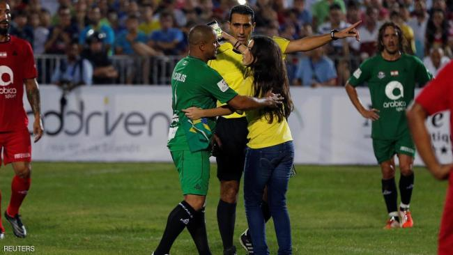 Former Brazilian soccer player Roberto Carlos greets a fan that ran onto the field during a friendly soccer match between International and Lebanese football stars in an event called the Game of Legends in Beirut, Lebanon September 10, 2016. REUTERS/Mohamed Azakir