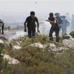 Palestinian protesters run in front of Israeli troops during clashes near the village of Deir Jarir near Ramallah