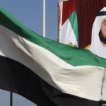 A United Arab Emirates flag waves in front of a big poster of President Sheikh Khalifa bin Zayed al-Nahayan in Abu Dhabi