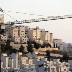 A crane is seen next to homes in a Jewish settlement near Jerusalem
