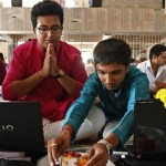 Businessmen offer prayers to Hindu gods in front of their laptops as part of a ritual to worship the Hindu deity of wealth Goddess Lakshmi on Diwali, in Ahmedabad
