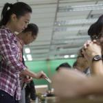 A woman presents her ID card to a poll assistant during a civil referendum held by the Occupy Central organisers at polling station in Hong Kong