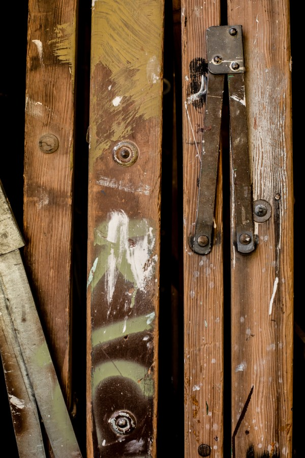 Photographic image of stacked ladders that have been splattered and brushed with paint.
